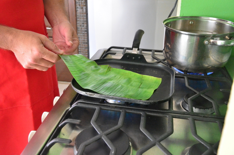 making the banana leaf pliable for the tamales
